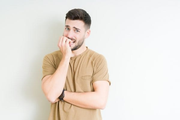 Man biting his nails because he has tics after head trauma