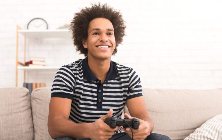 Young man smiling playing video games for TBI recovery
