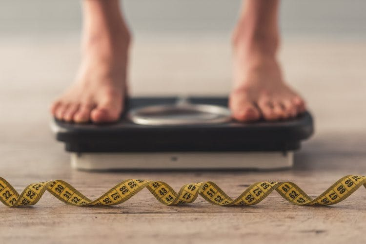 Cropped image of woman feet standing on weigh scales to measure her weight gain after brain injury. A tape measure lies on the floor in the foreground