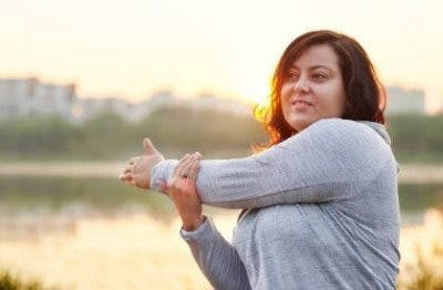 woman smiling and stretching shoulder in front of a lake at sunset