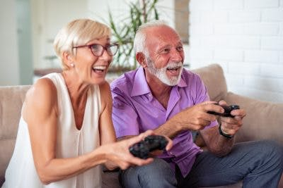 Happy senior couple playing video game for TBI recovery