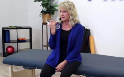 therapist holding water bottle adn demonstrating bicep exercises for brain injury recovery