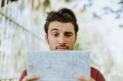 man struggling to read map because he has Gerstmann Syndrome, a symptom of parietal lobe damage