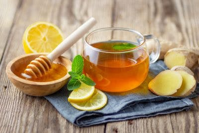 A glass cup of tea with lemon, mint and ginger