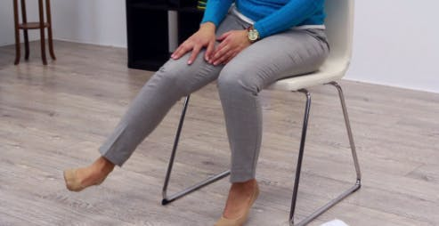 therapist kicking leg outward for foot drop exercise