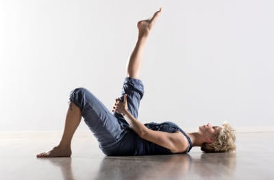 woman lying on floor stretching legs for physical therapy at home
