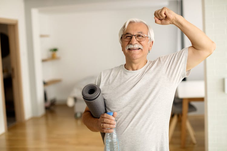 healthy mild stroke survivor holding a yoga mat after exercising at home