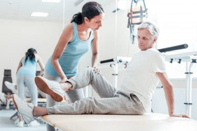therapist helping man with muscle twitching after brain injury sit up on table