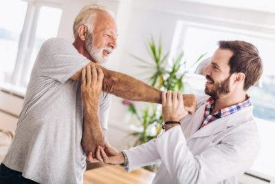 man doing his arm exercises with physical therapist