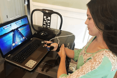 woman with brain injury using MusicGlove video game for TBI