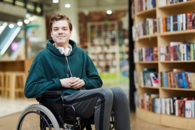 college student in wheelchair in library smiling because he has learned how to accommodate his traumatic brain injury in the classroom