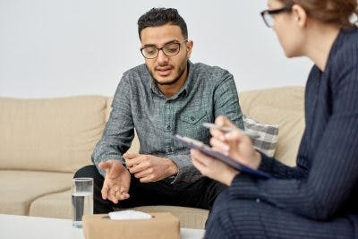 young man in psychologist office, learning how to overcome tics after head trauma