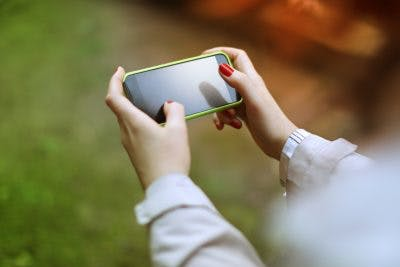 Woman playing puzzle game on smartphone