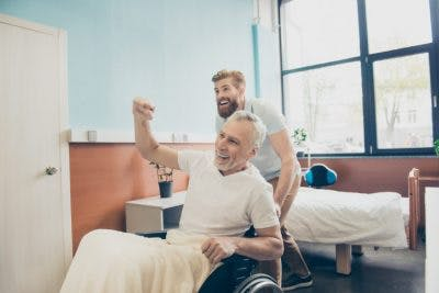 adult grandson wheeling grandfather out of hospital room while grandfather cheers