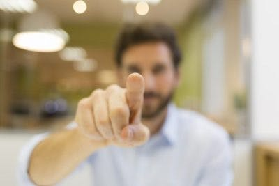 man pointing finger at camera, his finger is clear and in focus, but his face and everything behind him is out of focus