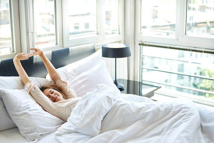 woman stretching in bed after a nap to help mood swings after stroke