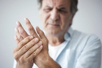 man holding hand and wincing because he has spasticity