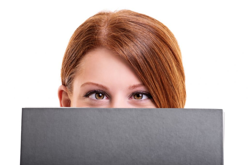 Close up shot of a young female student hiding her face behind a notebook, making funny face and crossing her eyes because she has double vision after head injury,