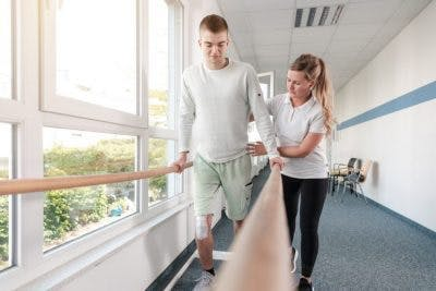 young man using parallel bars in rehab hospital, learning to walk because of stem cell therapy for brain injury