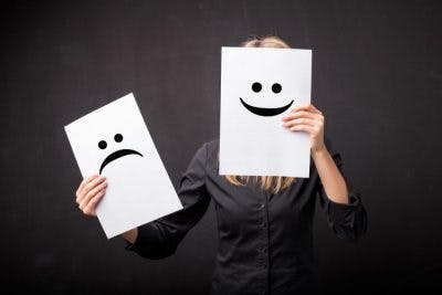 woman wearing black shirt in front of black background holding a smiley face and sad face picture in front of her face to represent pseudobulbar affect