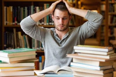 college student surrounded by books in library looking overwhelmed