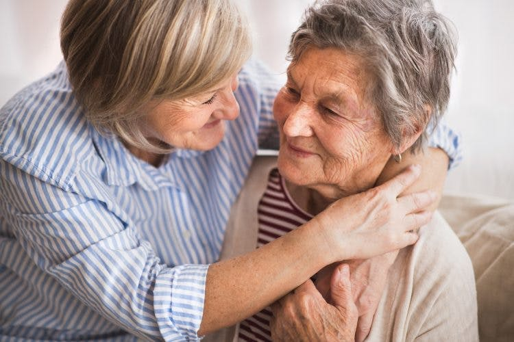 woman giving hug to a patient struggling with mood swings after stroke