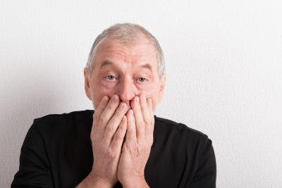 old man covering his mouth over his hands because he has just said something rude