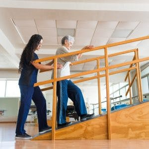 physiotherapist helping woman with rehab exercises to walk again