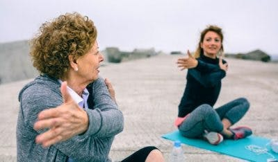 elderly stroke patient and daughter stretching on yoga mats on beach
