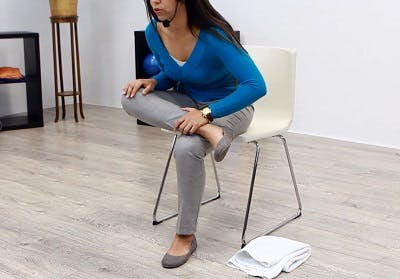 therapist sitting in chair showing balance exercises for stroke patients
