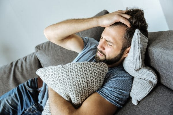 man laying on couch clutching pillow and pulling his hair because he has agitation after traumatic brain injury