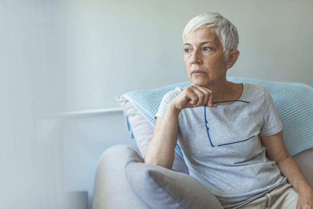 senior woman looking out window, absorbed in thought because she has anxiety after stroke