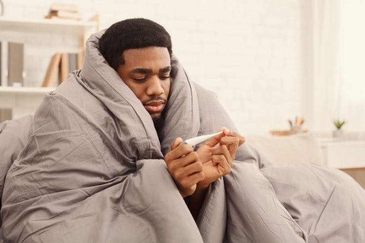 man wrapped in heavy blankets reading his temperature because he is feeling cold after head injury