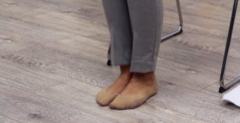 Therapeut auf einem Stuhl mit flachen Füßen auf dem Boden