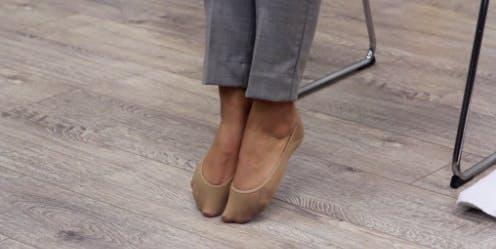 Die Zehen zeigten mit den Fersen vom Boden, um eine Fußtropfen-Therapie durchzuführen
