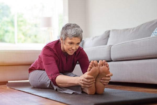 Woman doing floor exercises and stretching her feet because she has foot drop after TBI