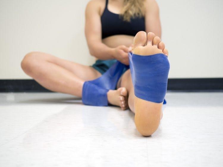 Frau mit Widerstandsband um den Fuß während der Physiotherapie