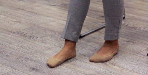 Physiotherapeut mit flachen Füßen auf dem Boden und einem Fuß nach vorne