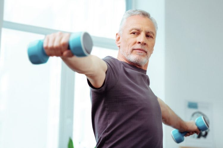 strong elderly man lifting dumbbells because he experienced spontaneous recovery after stroke