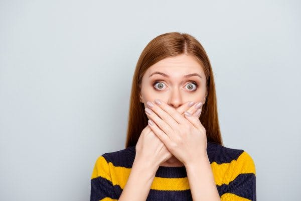woman covering her mouth to hide her stuttering after head injury