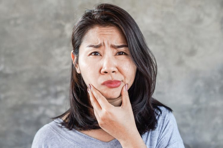 depressed Asian woman having problem with Facial Palsy after corpus callosum injury, hand holding her face