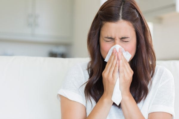 woman sneezing into tissue because she has a weak immune system after TBI