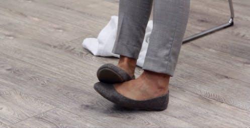 Therapeutin zeigt Fußtropfenübungen, indem sie ihren Fuß mit dem anderen Fuß anhebt
