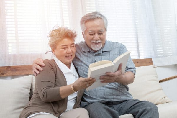 elderly married couple reading stroke recovery books together on a sofa