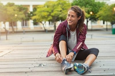 woman sitting on board walk putting on her running shoes
