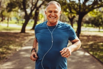 senior man smiling and jogging in park