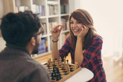 couple playing chess, woman is laughing because she captured a piece