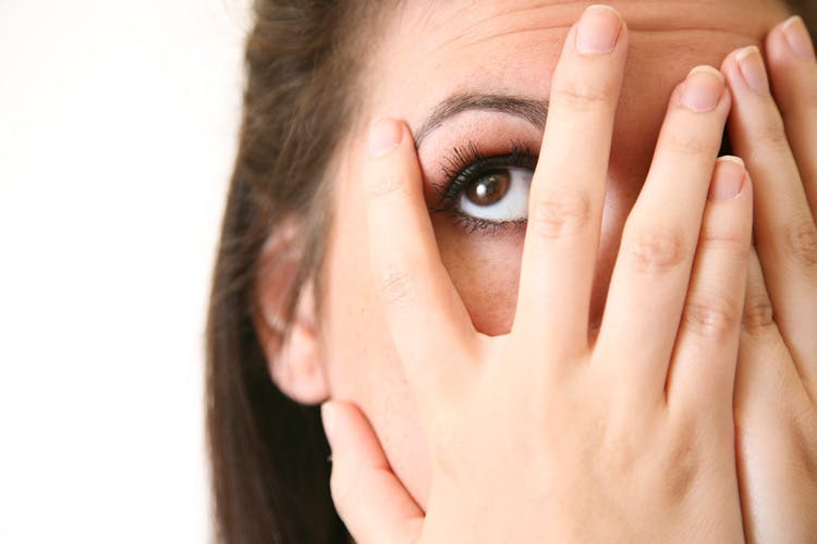 woman with left visual field cuts covering right eye and peeking out from left hand