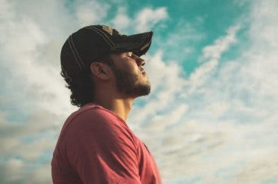 man standing outside, closing eyes and taking deep breaths to reduce his agitation after traumatic brain injury