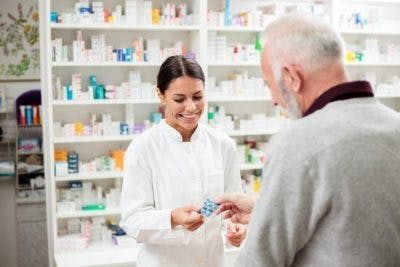 pharmacist handing customer medication for foot drop after TBI